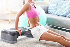 Sporty woman using step platform at home Stock Image