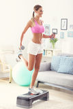 Sporty woman using step platform at home Royalty Free Stock Photos