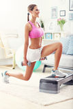 Sporty woman using step platform at home Royalty Free Stock Photo