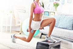 Sporty woman using step platform at home Royalty Free Stock Images