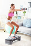 Sporty woman using step platform at home Royalty Free Stock Image
