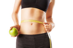 Sporty woman waist with measure tape and green apple Royalty Free Stock Image