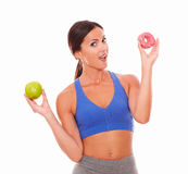 Sporty woman wanting to eat sugary cake Stock Photos