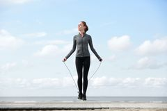 Sporty woman warming up with jump rope Stock Image