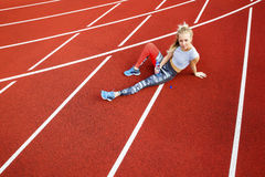 Sporty Woman With Water Bottle Sitting On Running Tracks Royalty Free Stock Photography