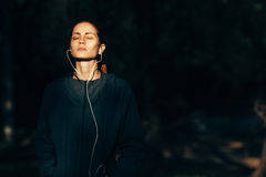 Sporty woman wearing hood jacket and listening music Royalty Free Stock Photo
