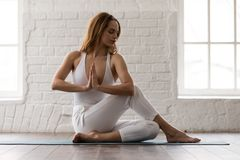 Sporty woman practicing yoga, sitting in Ardha Matsyendrasana pose. Sporty woman in white sportswear, pants and top practicing yoga, sitting in Ardha stock photo
