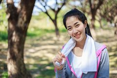 Sporty woman with white towel resting after workout sport exerci. Young sporty woman with white towel resting after workout sport exercises outdoors at the park Stock Image