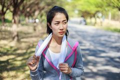Sporty woman with white towel resting after workout sport exerci. Young sporty woman with white towel resting after workout sport exercises outdoors at the park Royalty Free Stock Photo