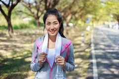 Sporty woman with white towel resting after workout sport exerci. Young sporty woman with white towel resting after workout sport exercises outdoors at the park Stock Photography