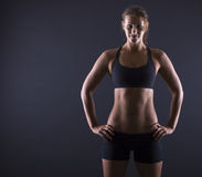 Sporty woman. A young woman carries athletic exercises on a dark background Stock Photos