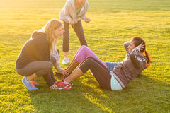 Sporty women doing sit ups during fitness class. In parkland Royalty Free Stock Image