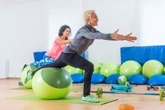 Sporty women doing stretching exercises with fitness stability ball in a sports club.  Stock Image