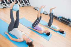 Sporty women holding balls between ankles in fitness studio Stock Image