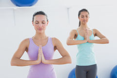 Sporty women with joined hands in fitness studio Royalty Free Stock Photos