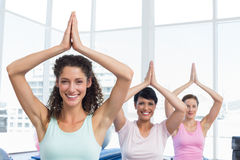 Sporty women with joined hands over head at fitness studio Stock Images