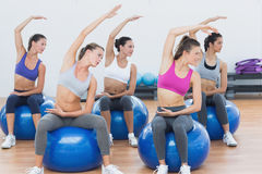 Sporty women stretching out hand on exercise balls at gym Stock Photos