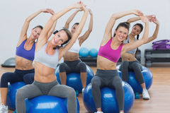Sporty women stretching up hands on exercise balls at gym Royalty Free Stock Photo
