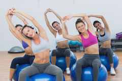 Sporty women stretching up hands on exercise balls at gym Royalty Free Stock Photography
