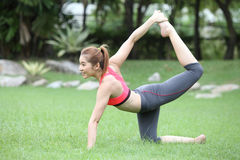 Sporty yoga girl doing exercises for buttocks on lawn Stock Images