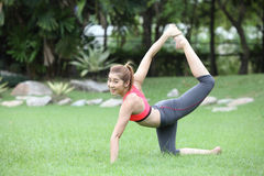 Sporty yoga girl doing exercises for buttocks on lawn Stock Image