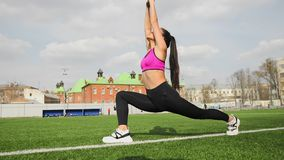 Sporty young asian woman is stretching on the stadium. Sports workout outdoors. Sporty young asian woman is stretching on the stadium. Sports and fitness stock video footage