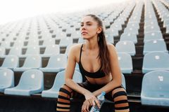 Sporty young attractive girl in sportswear relaxing after hard workout sit and drink water from bottle after running on a stadium. Summer workout royalty free stock photography