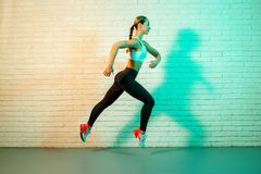 Sporty young attractive woman jogging front brick wall in neon lights. royalty free stock images