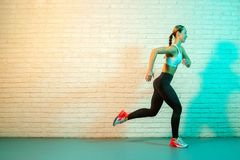 Sporty young attractive woman jogging front brick wall in neon lights. stock photos