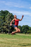 Sporty young blond woman jumping for happiness outdoors Royalty Free Stock Image