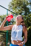 Sporty young blonde woman with sporty glass with cool illuminating water pours water on herself on sports field. Sporty young blonde woman with a sporty glass stock image