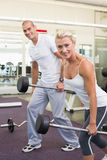 Sporty young couple lifting barbells in gym Royalty Free Stock Image