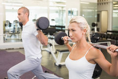 Sporty young couple lifting barbells in gym Stock Photo