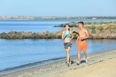 Sporty young couple running on sea beach. At resort Royalty Free Stock Photo