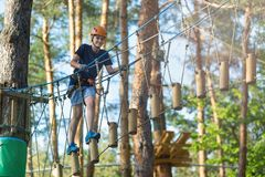 Sporty, young, cute boy in white t shirt spends his time in adventure rope park in helmet and safe equipment in the park royalty free stock photos