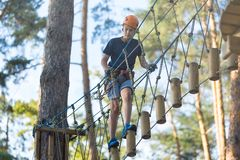 Sporty, young, cute boy in white t shirt spends his time in adventure rope park in helmet and safe equipment in the park royalty free stock images