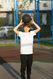Sporty, young, cute, healthy boy plays basketball on the sports playground at sunny summer royalty free stock photos