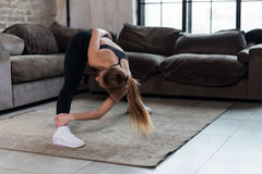 Sporty young female doing stretching exercise bending forward during home workout stock image