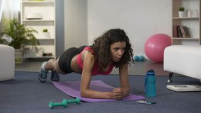 Sporty young female setting stopwatch, doing plank exercise and checking time
