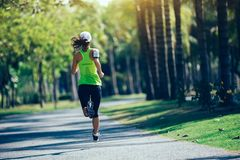 Young fitness woman running at tropical park Stock Photo