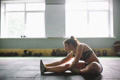Sporty young girl doing warm-up, stretching muscles on the floor in gymnasium in backlight from window Stock Photo