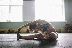 Sporty young girl doing warm-up, stretching muscles on the floor in gymnasium in backlight from window Royalty Free Stock Photos