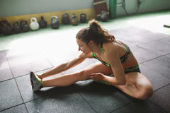 Sporty young girl doing warm-up, stretching muscles on the floor in gymnasium in backlight from window Stock Image