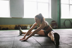 Sporty young girl doing warm-up, stretching muscles on the floor in gymnasium in backlight from window Stock Photography