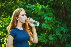 Sporty young girl drinks water from a bottle on a background of bright foliage royalty free stock photo