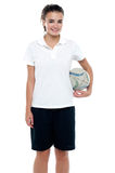 Sporty young girl holding a rugby ball Royalty Free Stock Image