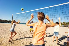 Sporty young girl passing volleyball over the net. Sporty teenage girl passing the ball over the net during beach volleyball match at sunny day royalty free stock photography