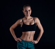 Sporty young girl in sportswear showing muscles on black background. Tanned young athletic woman. A great sport female body. Stock Images
