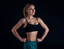 Sporty young girl in sportswear showing muscles on black background. Tanned young athletic woman. A great sport female body. Stock Photo