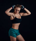 Sporty young girl in sportswear showing muscles on black background. Tanned young athletic woman. A great sport female body. Royalty Free Stock Photography